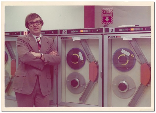 "My father writes: ""Well, the guy leaning up against the tape drives of a Sperry-UNIVAC Model 70, is me - circa 1975 or so. Each drive was about the size of a refrigerator, and we had 6 of them. (The company published 27 magazines and needed a lot of tape storage.) These were high quality drives and could store 150 mb or so on a 2400' reel. Cheap ones could store only 10 mb. I'm leaning on drive number 1 – yet there's a drive behind me. Why? In those days, numbering schemes began with 0."""